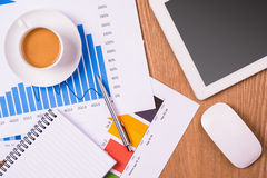 Blank notepad, coffee cup over charts and tablet on wooden table Royalty Free Stock Photo