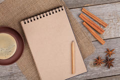 Blank notepad with coffee cup and spices on wooden table Royalty Free Stock Image
