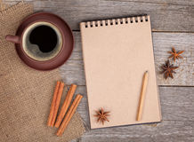 Blank notepad with coffee cup and spices on wooden table Royalty Free Stock Photography