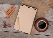 Blank notepad with coffee cup and spices on wooden table Royalty Free Stock Images