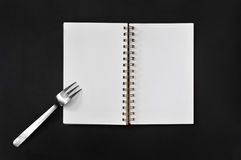 Blank notepad with fork on black background Royalty Free Stock Images