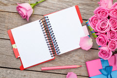 Blank notepad and gift box full of pink roses Stock Photos