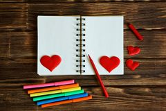 Blank notepad with hearts and multi-colored felt-tip pens on a wooden background. Preparation for congratulations on Valentines stock photography