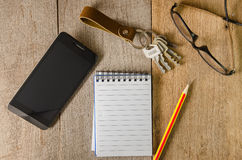 Blank notepad, key chain, eye glasses and mobile phone on wooden Stock Photos