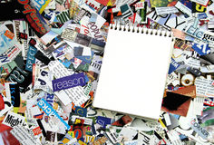 Blank Notepad and magazine clippings. Blank notepad on a background of magazine text clippings Royalty Free Stock Images
