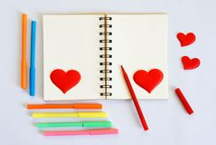 Blank notepad with multicolored felt-tip pens and red hearts on a white background. Template for Valentine`s Day greetings. stock photo