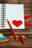 Blank notepad with multicolored felt-tip pens and red hearts on wooden background. Preparation for congratulations on Valentine`s stock images