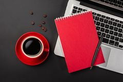 Blank notepad over laptop and coffee cup on office black table. Top view with copy space stock photography