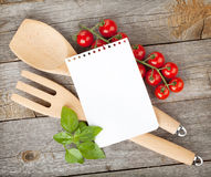 Blank notepad paper for your recipes with tomatoes and basil. On wooden table Royalty Free Stock Photography