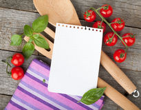 Blank notepad paper for your recipes with tomatoes and basil. On wooden table Stock Images