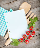 Blank notepad paper for your recipes. With tomatoes and basil on wooden table Royalty Free Stock Photography