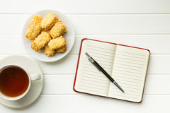 Blank notepad with pen and cookies with tea. Stock Image