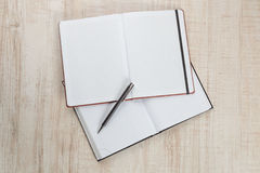 Blank notepad with pen on office wooden table Stock Images