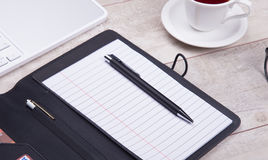Blank notepad with pen on office wooden table Royalty Free Stock Images