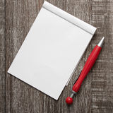 Blank notepad and pen on wooden table stock photography