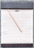 Blank notepad with pencil on the brown clipboard. Royalty Free Stock Image
