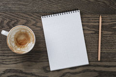 Blank notepad with pencil and empty coffee cup on wooden table Stock Photos