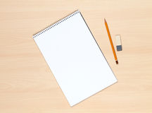 Blank notepad, pencil and eraser on the wooden table Royalty Free Stock Photos