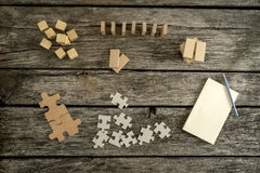Blank notepad, pencil and piles of puzzle pieces, wooden blocks Royalty Free Stock Photography