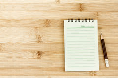 Blank notepad with  pencil on wooden table Royalty Free Stock Images