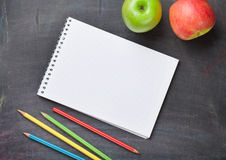 Blank notepad, pencils and apples on blackboard Royalty Free Stock Photo