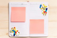 Notepad - top view. Blank notepad with pills on the wooden table. View from above Royalty Free Stock Photography