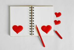 Blank notepad with red felt-tip pen and red hearts on a white background. Template for Valentine`s Day greetings royalty free stock photo