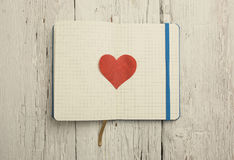 Blank notepad with red heart on wood Stock Images