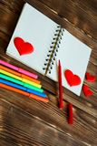 Blank notepad with red hearts and multi-colored felt-tip pens on a wooden background. Preparation for congratulations on Valentine royalty free stock images
