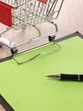 Blank notepad with a shopping cart Royalty Free Stock Image