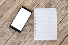 Blank notepad and Smart phone with blank screen and can be add y. Our texts or others on notepad and smart phone.selective focus Royalty Free Stock Photo