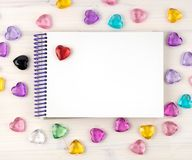 Blank notepad on spirals. Place for text. Around colored decorative hearts. Mok up stock photography