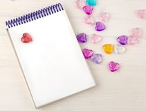 Blank notepad on spirals. Place for text. Around colored decorative hearts. Mok up royalty free stock image