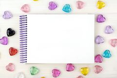 Blank notepad on spirals. Place for text. Around colored decorative hearts. Mok up royalty free stock photography
