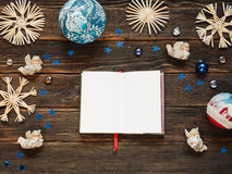 A blank notepad surrounded by Christmas decoration or baubles, s. Traw snowflakes, angels and small blue stars on a dark wooden background, add copy or graphic Stock Photos