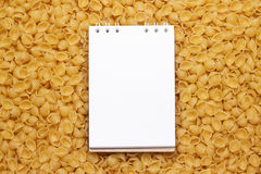 Blank notepad on uncooked macaroni background Stock Image