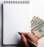 Blank notepad with US currencies. Blank notepad with hand holding pen and US currencies Royalty Free Stock Photos