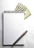 Blank notepad with US currencies. Blank notepad with pen and US currencies Royalty Free Stock Images