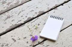 Blank notepad and violet flower on rustic plank wood background Stock Photo