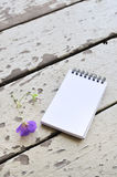 Blank notepad and violet flower on rustic plank wood background Stock Image