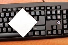 Blank notepaper. The blank notepaper on black keyboard royalty free stock photo