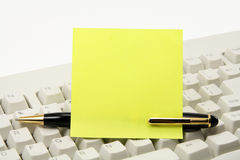Blank notepaper stick on a pen with keyboard. Blank notepaper stick on a pen and keyboard with white background Royalty Free Stock Image