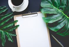 Blank notepaper with tropical leaves and accessories laying on table. Blank notepaper with tropical leaves and accessories laying on black table.Home office Stock Image