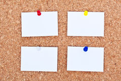 Blank notes on bulletin board. Four blank notes with pushpins on a bulletin board Royalty Free Stock Images