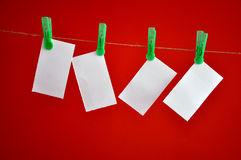 Blank notes hanging clipped on red background Stock Photo