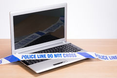 Blank office laptop and police crime scene tape. An open, blank office computer laptop on a plain timber desk with police crime scene tape draped across the royalty free stock photography