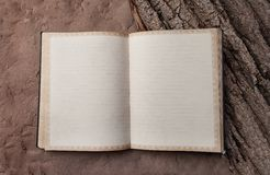 Blank old book in the clear on the sand and tree bark. Notebook Stock Photo