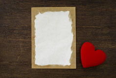 Blank old paper card and red heart on vintage wood background Royalty Free Stock Photo