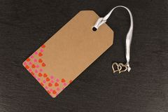 Blank old paper cloth tag or label isolated on a dark slate background. Heart shape pattern royalty free stock photo