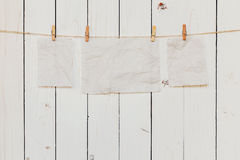 Blank old paper hanging on white wood background with space for. Text Royalty Free Stock Images